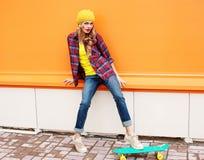 Forme a la mujer bonita que lleva la ropa colorida casual con el patín Fotografía de archivo libre de regalías