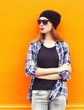 Forme a la mujer bonita que lleva un sombrero negro, las gafas de sol y la camisa sobre fondo colorido Fotografía de archivo