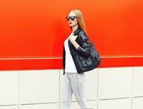 Forme a la mujer bonita que lleva una chaqueta, las gafas de sol y el bolso del negro de la roca en perfil sobre rojo Fotos de archivo libres de regalías