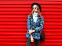 Forme a la mujer bonita que lleva una chaqueta y un bolso de la capa del sombrero negro sobre rojo colorido fotos de archivo