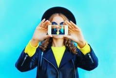 Forme a la mujer bonita que toma el autorretrato de la foto en smartphone sobre azul colorido Foto de archivo libre de regalías