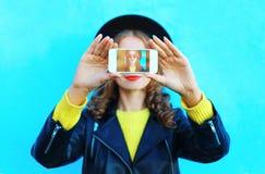 Forme a la mujer bonita que toma el autorretrato de la foto en smartphone sobre colorido azul Imagen de archivo libre de regalías