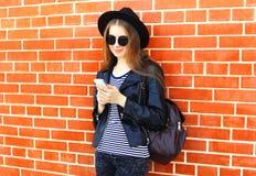 Forme a la mujer bonita que usa smartphone en estilo del negro de la roca sobre fondo de los ladrillos Fotos de archivo