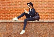 Forme a la mujer bonita que usa smartphone en estilo del negro de la roca sobre fondo de los ladrillos Imagen de archivo