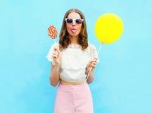 Forme a la mujer con el balón y la piruleta de aire que se divierten sobre azul colorido Foto de archivo