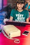 Forme a la mujer con el bolso de lujo del pitón del snakeskin en la tabla de madera en restaurante Isla de Bali Imagenes de archivo