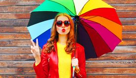 Forme a la mujer con el paraguas colorido en un día del otoño Foto de archivo