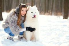 Forme a la mujer con el samoyedo del perro en bosque del invierno Imágenes de archivo libres de regalías