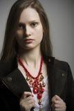 Forme a la mujer con la chaqueta negra y el collar brillante hermoso del color rojo Imagen de archivo libre de regalías