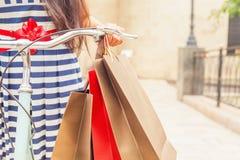 Forme a la mujer con los bolsos y bike, viaje que hace compras a Italia Fotografía de archivo libre de regalías