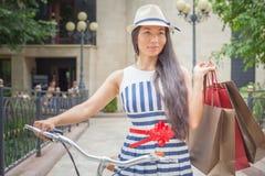 Forme a la mujer con los bolsos y bike, viaje que hace compras a Italia Imagen de archivo libre de regalías