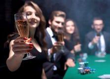 Forme a la mujer con los vidrios de vino, sentándose en una tabla en un casino foto de archivo