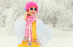 Forme a la mujer del invierno que habla en el smartphone que lleva la bufanda hecha punto colorida del sombrero sobre fondo nevos Fotos de archivo
