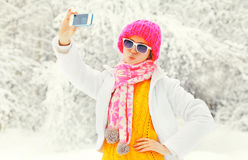 Forme a la mujer del invierno que toma el autorretrato de la foto en smartphone sobre los árboles nevosos que llevan una bufanda  Foto de archivo libre de regalías