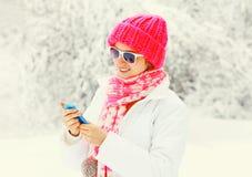 Forme a la mujer del invierno que usa el smartphone que lleva la bufanda hecha punto colorida del sombrero sobre nevoso Imágenes de archivo libres de regalías
