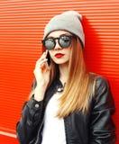 Forme a la mujer del retrato que habla en smartphone en ciudad sobre rojo Fotos de archivo libres de regalías