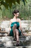 Forme a la mujer delgada que lleva el vestido corto sin tirantes verde que se sienta en las escaleras viejas y sucias del cemento fotografía de archivo