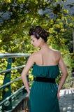 Forme a la mujer delgada que lleva el vestido verde que se opone al puente fotografía de archivo libre de regalías