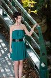 Forme a la mujer delgada que lleva el vestido verde que se opone al puente imagen de archivo libre de regalías