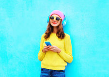 Forme a la mujer despreocupada que escucha la música en auriculares con el smartphone que lleva un suéter rosado colorido de las  Fotografía de archivo
