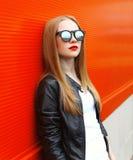 Forme a la mujer elegante que lleva un negro de la roca la chaqueta de cuero y las gafas de sol Foto de archivo libre de regalías