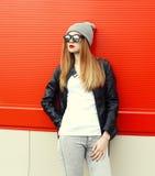 Forme a la mujer elegante que lleva un negro de la roca la chaqueta de cuero y las gafas de sol con el sombrero Foto de archivo