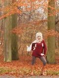 Forme a la mujer en bosque ventoso del parque del otoño de la caída Foto de archivo