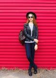 Forme a la mujer en el estilo negro de la roca que presenta sobre rosa Imagen de archivo