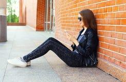Forme a la mujer en el estilo negro de la roca que se sienta usando smartphone sobre fondo Imagen de archivo