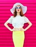 Forme a la mujer en el sombrero y la falda blancos de paja del verano sobre rosa colorido Imagen de archivo