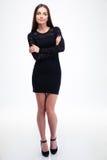 Forme a la mujer en el vestido negro que se coloca con los brazos doblados Fotografía de archivo libre de regalías