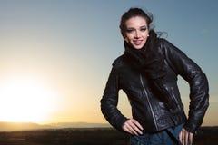 Forme a la mujer en la chaqueta de cuero que presenta con las manos en caderas y el SM Imagen de archivo
