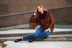Forme a la mujer en la chaqueta de cuero que se sienta en la calle de la ciudad Imagenes de archivo
