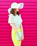 Forme a la mujer en sombrero de paja del verano con el embrague del bolso sobre rosa colorido Imagenes de archivo