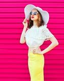 Forme a la mujer en sombrero y falda de paja del verano sobre rosa colorido Fotografía de archivo libre de regalías