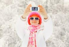 Forme a la mujer feliz del invierno que toma el autorretrato de la foto en smartphone sobre árbol nevoso Fotos de archivo libres de regalías