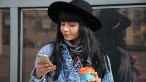 Forme a la mujer hermosa de Latina el hispanico que manda un SMS en smartphone en el café de consumición del latte de la ciudad almacen de video