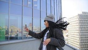 Forme a la mujer hermosa de Latina el hispanico que manda un SMS en smartphone en el café de consumición del latte de la ciudad almacen de metraje de vídeo