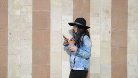 Forme a la mujer hermosa de Latina el hispanico que manda un SMS en smartphone en el café de consumición del latte de la ciudad metrajes