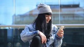 Forme a la mujer hermosa de Latina el hispanico que manda un SMS en smartphone en la ciudad metrajes