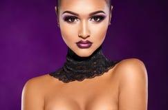 Forme a la mujer hermosa en el fondo púrpura que mira la cámara Imagenes de archivo