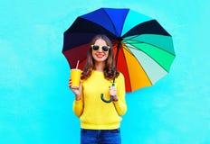 Forme a la mujer joven bastante sonriente con la taza del zumo de fruta fresca y el paraguas colorido en día del otoño sobre fond Fotografía de archivo