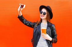 Forme a la mujer joven bastante sonriente que toma el autorretrato de la imagen en smartphone en estilo negro de la roca sobre ro Foto de archivo