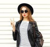 Forme a la mujer joven con el bolso de la mochila en estilo negro de la roca sobre blanco Imagen de archivo