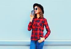 Forme a la mujer joven con la taza de café que descansa al aire libre en la ciudad, llevando la camisa a cuadros roja del sombrer Foto de archivo