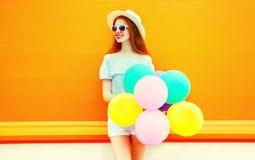 Forme a la mujer joven con los globos coloridos de un aire en una naranja Imagenes de archivo