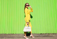 Forme a la mujer joven elegante en ropa amarilla del traje con el bolso Imagen de archivo