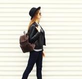 Forme a la mujer joven en estilo negro de la roca que camina en ciudad sobre el perfil blanco de la opinión del fondo Fotos de archivo