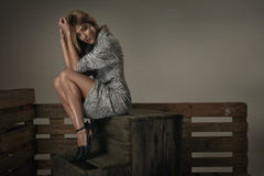 Forme a la mujer joven natural que se sienta en un pecho de madera imagen de archivo