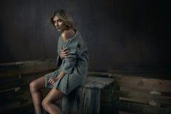 Forme a la mujer joven natural que se sienta en un pecho de madera foto de archivo libre de regalías